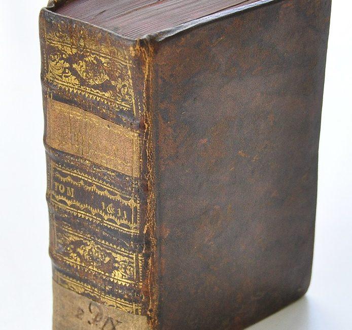 Oryginalna tekturowo-skórzana oprawa dwutomowego wydania rozprawy Woltera ze złoceniami i szyldzikami (1751)